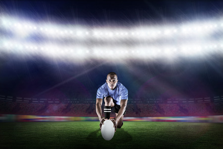 rugby ball: Portrait of rugby player kneeling and holding ball against rugby stadium Stock Photo