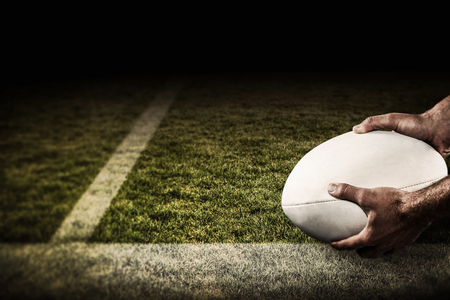 player: Sports player holding ball against pitch Stock Photo