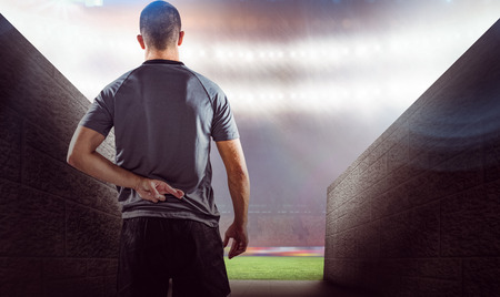 fingers: Rear view of rugby player with fingers crossed against rugby stadium