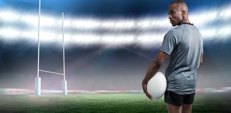 pelota rugby: Vista trasera del atleta confía en pie con pelota de rugby contra el estadio de rugby