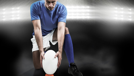 by placing: Full length of rugby player placing ball against spotlight Stock Photo