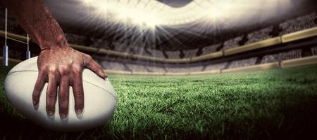 pelota: Primer plano de jugador de los deportes que sostiene la bola contra el campo de rugby