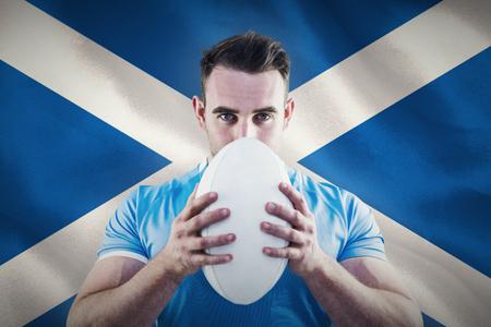 scottish flag: Giocatore di rugby guardando la fotocamera con palla contro primo piano della bandiera scozzese