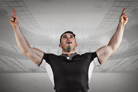 winning pitch: Rugby player cheering and pointing against grey vignette