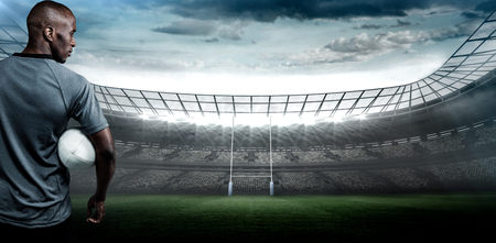 stadium lights: Rear view of sportsman with rugby ball against rugby stadium
