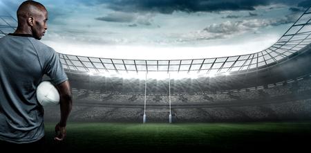 pelota rugby: Vista posterior de la deportista con pelota de rugby contra el estadio de rugby