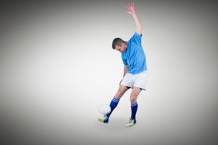 kicking: Rugby player kicking a rugby ball against grey vignette Stock Photo