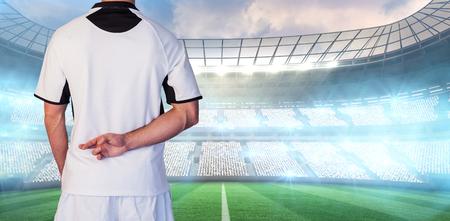 bonhomme blanc: Vue arri�re de joueur de rugby avec les doigts crois�s contre stade de rugby Banque d'images