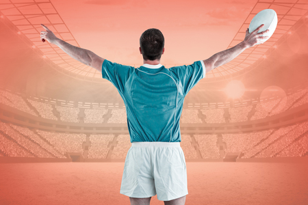 turned out: Rugby player gesturing with hands against orange Stock Photo