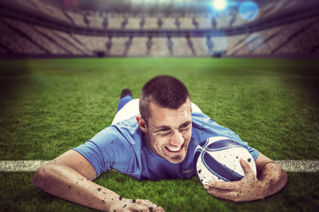 world player: Confident rugby player lying in front with ball against large football stadium with lights