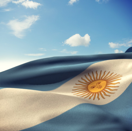 argentina flag: Argentina flag waving in wind against blue sky with clouds Stock Photo