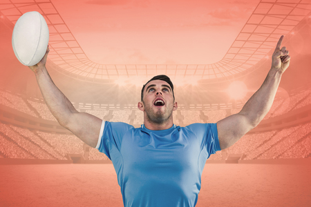 winning pitch: Rugby player cheering and pointing against orange Stock Photo