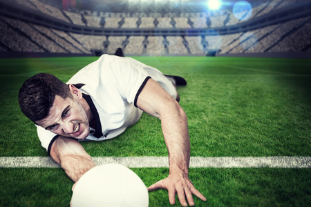 down lights: Man lying down while holding ball against large football stadium with lights