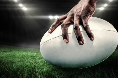 and rugby ball: Cropped image of sportsman holding rugby ball against rugby stadium