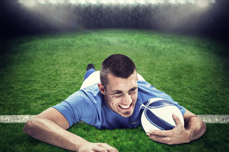 rugby: Confident rugby player lying in front with ball against rugby stadium Stock Photo
