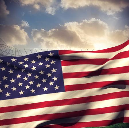 bandera blanca: Waving American flag against large football stadium under cloudy blue sky Foto de archivo