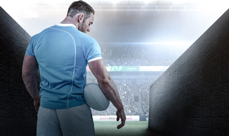 rugby player: Rugby player standing with ball against rugby stadium Stock Photo