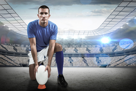 rugby: Full length portrait of rugby player placing ball against rugby stadium Stock Photo