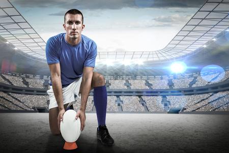 pelota rugby: Retrato de cuerpo entero de jugador de rugby que coloca la pelota contra el estadio de rugby Foto de archivo