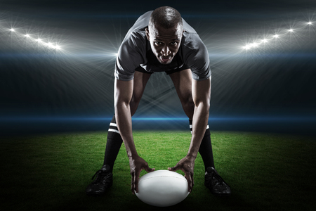 rugby ball: Portrait of sportsman holding ball while playing rugby against rugby stadium