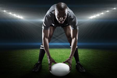 pelota rugby: Retrato de deportista que sostiene la bola durante la reproducción de rugby contra estadio de rugby