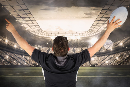 winning pitch: Back turned rugby player gesturing victory against large football stadium with lights Stock Photo