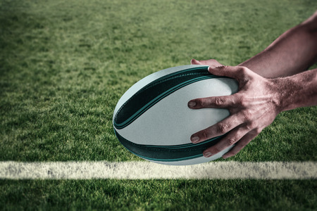 world player: Cropped image of sports player holding ball against rugby pitch