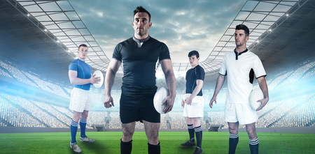 rugby field: Rugby player holding rugby ball against soccer stadium