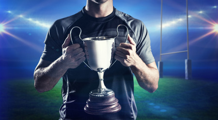 the victorious: Victorious rugby player holding trophy against rugby stadium