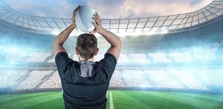 turned: Back turned rugby player throwing a ball against rugby stadium