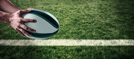 sportsperson: Cropped image of sports player holding ball against rugby pitch