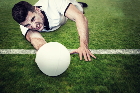 man lying down: Man lying down while holding ball against green field