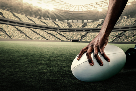pelota: Imagen recortada de atleta sosteniendo pelota de rugby contra el estadio de rugby