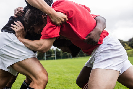 scrum: Rugby players doing a scrum at the park