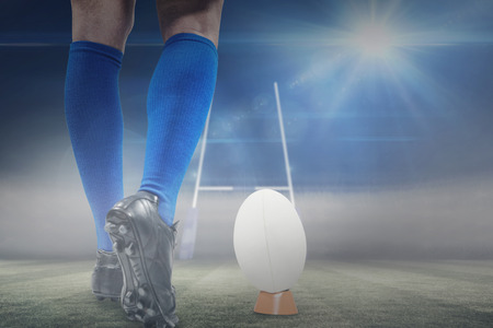 world player: Low section of rugby player about to kick the ball against rugby pitch