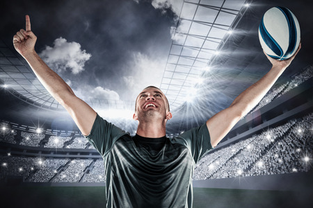 and rugby ball: Successful rugby player holding ball with arms raised against football stadium with fans in white