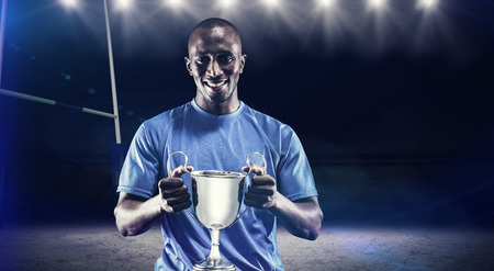 winning pitch: Portrait of happy athlete holding trophy against rugby stadium