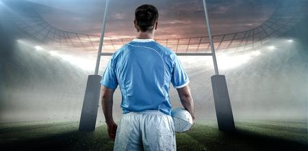 and rugby ball: El jugador de rugby sosteniendo una pelota de rugby contra el estadio de rugby