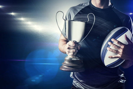 rugby: Midsection of successful rugby player holding trophy and ball against spotlights Stock Photo