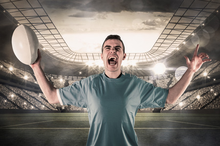 people shadow: A rugby player gesturing victory against large football stadium with lights