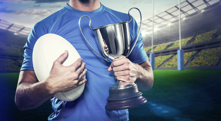 winning pitch: Rugby player holding trophy and ball against rugby stadium