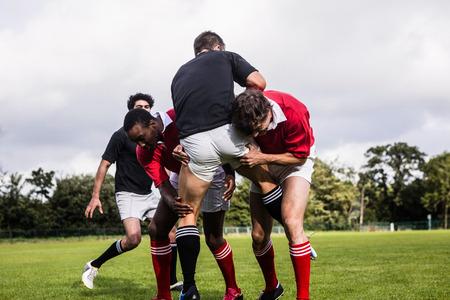Les joueurs de rugby attaquent pendant le jeu dans le parc