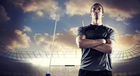 rugby: Confident rugby player with arms crossed against rugby stadium Stock Photo