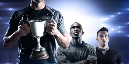 the victorious: Victorious rugby player holding trophy against spotlight