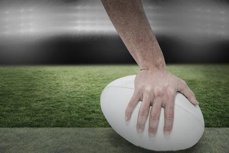 the football player: Primer plano de jugador de los deportes que sostiene la bola contra el centro de atenci�n Foto de archivo