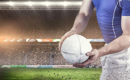 pelota rugby: El jugador de rugby a punto de tirar la pelota de rugby contra los aficionados al rugby en la arena