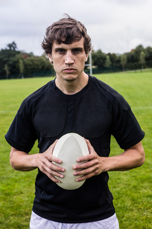scowling: Rugby player scowling at camera at the park Stock Photo