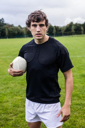 Rugby player scowling at camera at the park Stock Photo
