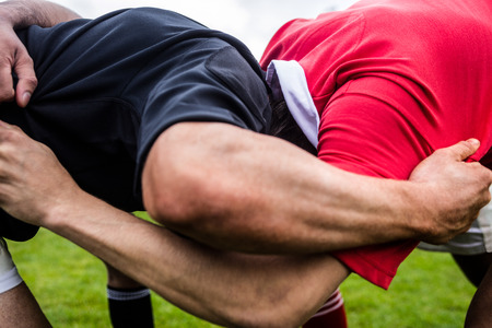 Rugby-Spieler macht einen Scrum im Park