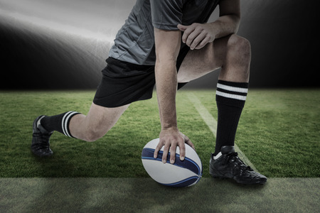 ball stretching: Rugby player in black jersey stretching with ball against spotlight Stock Photo
